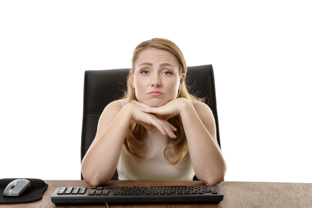 uninterested: businesswoman at her desk looking bored and uninterested in her work Stock Photo