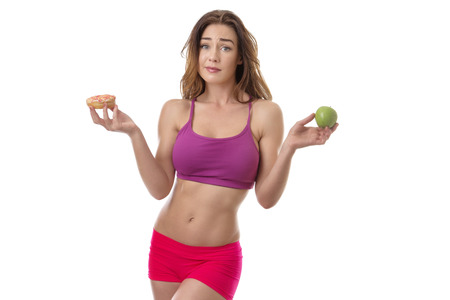 eat right: Slim fitness model deciding if she should eat the doughnut in her right hand or the apple in her left hand