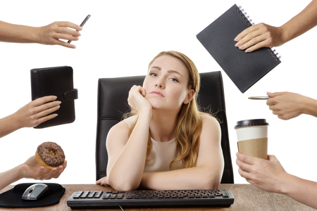 uninterested: businesswoman at her desk looking bored and uninterested in her work, surrounded by many hands with different objects in each hand Stock Photo
