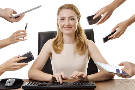hands work: businesswoman at her desk looking happy in her work, surrounded by many hands with different objects in each hand