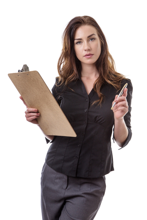 poised: Pretty brunette in a business suit poised with a clip board and a silver pen isolated on white. Stock Photo