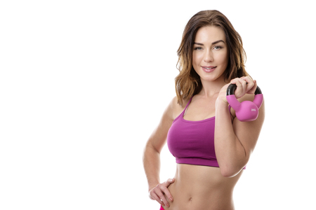 kettlebell: Close up studio shot of a pretty young model holding a pink kettlebell isolated on white