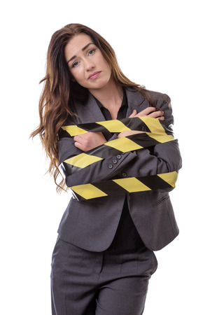 wrapped up: business woman wrapped up in yellow and black tape isolated on white Stock Photo