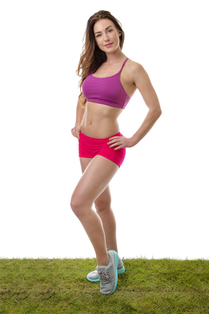 beauty full: Pretty young model wearing her fitness outfit with her left hand on her hip standing on the grass on an isolated white background