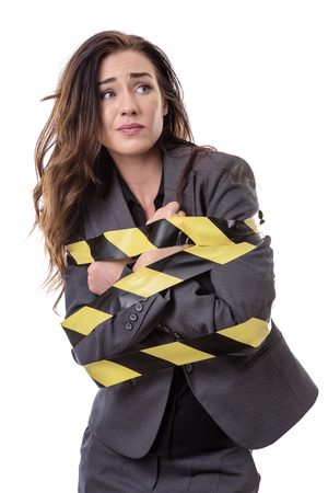 business woman wrapped up in yellow and black tape isolated on white Stock Photo