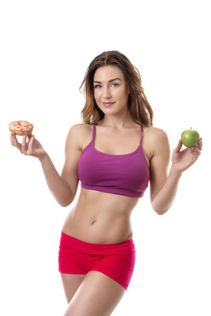 deciding: Slim fitness model deciding if she should eat the doughnut in her right hand or the apple in her left hand
