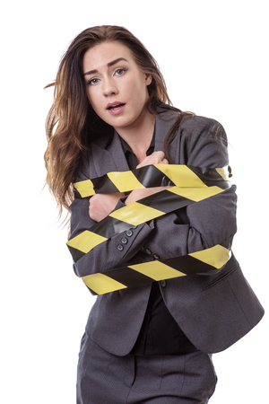 bound woman: business woman wrapped up in yellow and black tape isolated on white Stock Photo