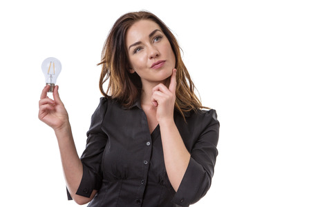 expressing: Pretty brunette holding onto a lightbulb, looking thoughtful Stock Photo