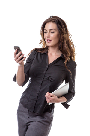 int: business model holding a mobile phone in one hand and her tablet computer int he other isolated on white.
