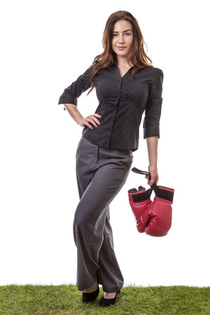 dominate: SLim model wearing a business suit, holding some boxing gloves in one hand, standing on grass. Stock Photo