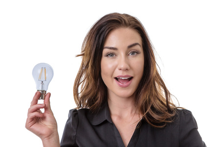 expressing: Pretty brunette holding onto a lightbulb, looking pleased with her idea.