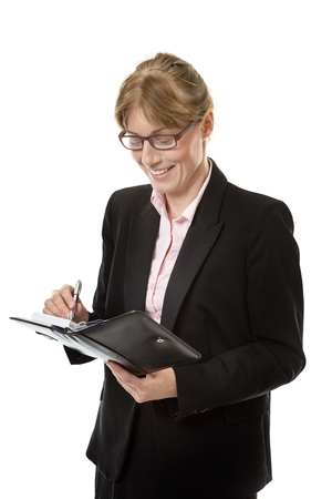 personal organiser: business woman wearing glasses is writing in her personal organiser isolated on white