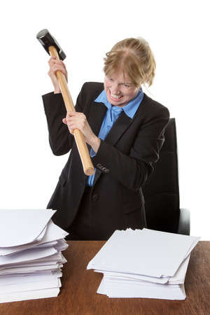 over burdened: Mature office worker holds a large hammer above a pile of paper work. Stock Photo