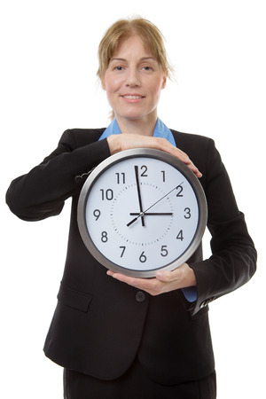 timekeeping: Confident mature caucasian business woman holding a large clock In her hands showing the success of good office timekeeping.
