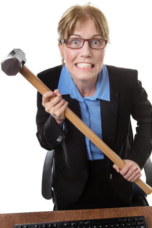 poised: frustrated office worker is holding a sledgehammer, poised ready to smash into her keyboard!