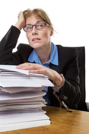 out of office: Stressed out office worker is handcuffed to her desk with a huge pile of paperwork, isolated on white. Stock Photo