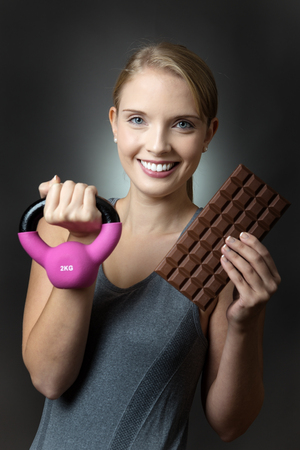 kettle bell: Close up shot of a pretty young fitness model holding a pink kettle bell and a large bar of chocolate, shot on a grey background