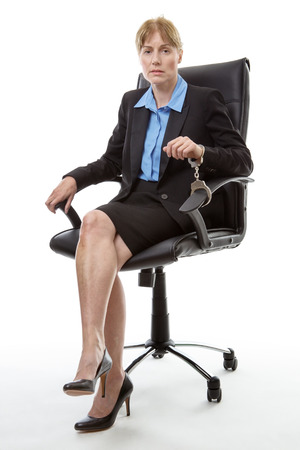 handcuffs: Mature business woman sitting in an office chair handcuffed to chair