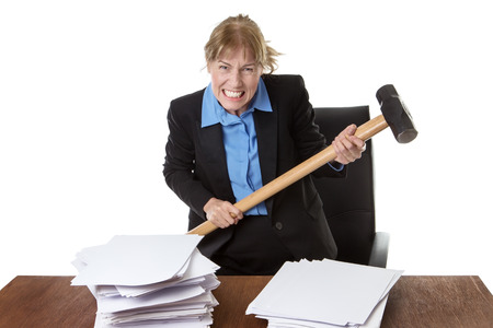 over burdened: Mature office worker holding a sledge hammer above a pile of paper work.