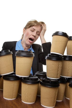 wornout: Very tired business woman is yawning whilst hiding behind many disposable cups. Studio shot isolated on white