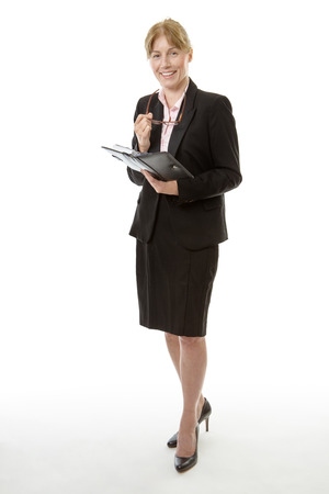 personal organiser: Full length shot of a business woman holding her glasses is writing in her personal organiser isolated on white Stock Photo