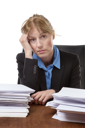 over worked: Over worked woman, rests her head on her hand, surrounded by big piles of paperwork, isolated on white