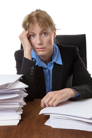 over worked: Over worked woman, rests her head on her hand, surrounded by big piles of paperwork.