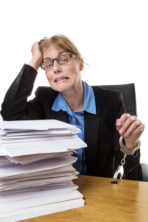 servitude: Stressed out office worker is handcuffed to her desk with a huge pile of paperwork Stock Photo