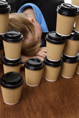 wornout: business woman has fallen asleep on the desk behind lots of takeaway drink cups.