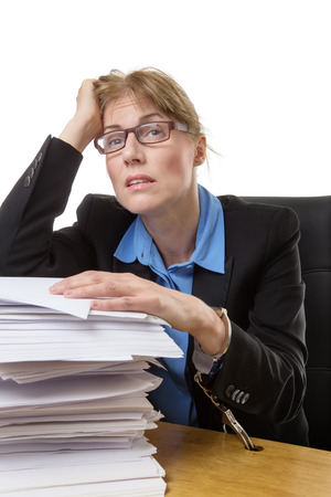 over burdened: Stressed out office worker is handcuffed to her desk with a huge pile of paperwork. Stock Photo