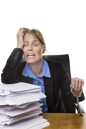 workload: Office shot of heavy workload concept with pile of paper and woman worrying about the amount of work. Stock Photo