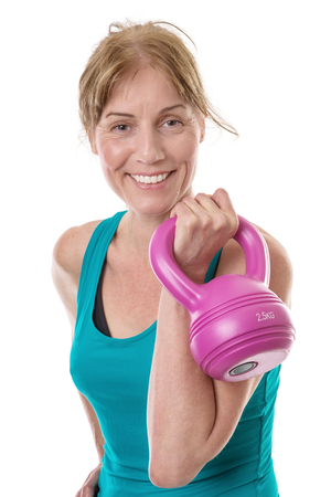 holding close: Close up shot of a fitness model holding a pink kettlebell in her left hand, isolated on white Stock Photo