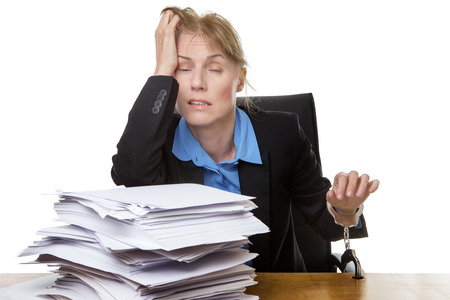 servitude: Office shot of heavy workload concept with pile of paper and woman worrying about the amount of work.  chained to desk Stock Photo