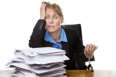 acoso laboral: Oficina tiro del concepto de carga de trabajo con la pila de papel y la mujer de preocuparse por la cantidad de trabajo. encadenado a la mesa Foto de archivo