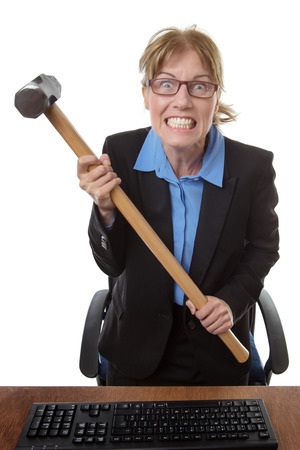 poised: frustrated office worker is holding a sledge hammer, poised ready to smash into her keyboard!