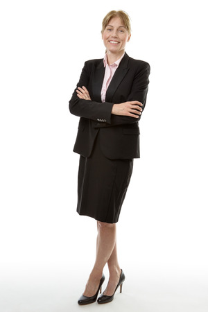 full shot: Full length studio shot of a woman in a business suit, with her arms folded, isolated on white. Stock Photo