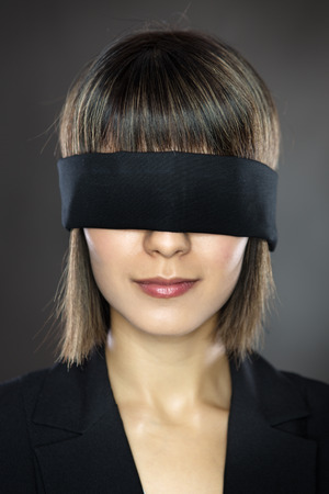 low key lighting: blind folded business woman low key lighting shot in the studio on a gray background Stock Photo