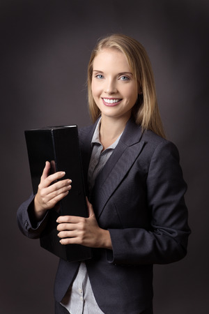 file box: Upper body shot of a smiling business model, holding a black box file. Shot on a grey background.