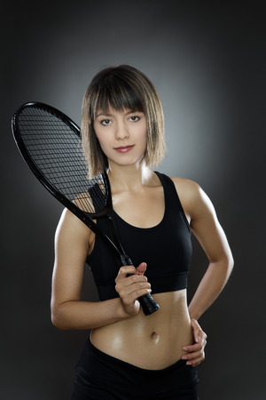 low key lighting: fitness woman shot in the studio low key lighting holding a tennis racket