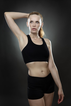 low key lighting: fitness woman shot in the studio with a gray background low key lighting