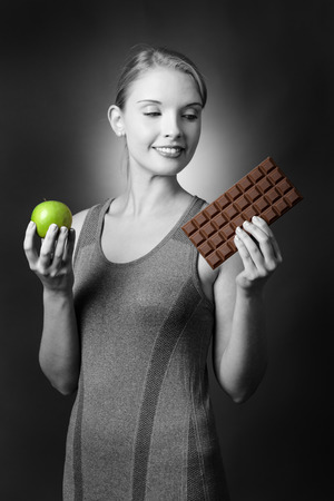 indulging: Studio shot of a pretty fitness model holding an apple in one hand and being tempted by a large bar of chocolate in the other.  Shot on a grey background.