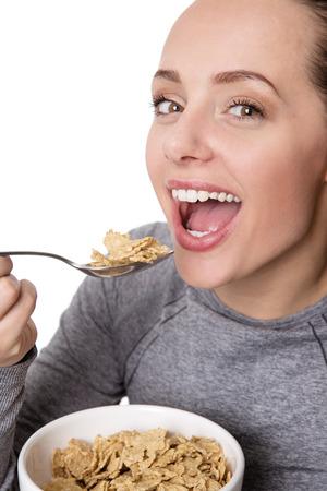 comiendo cereal: Mujer feliz llevando ropa de la aptitud que come el cereal Foto de archivo