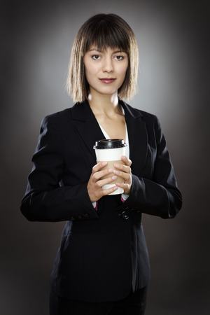 low key lighting: portrait of young sharply dressed business woman holding a take away cup shot in the studio low key lighting on a gray background Stock Photo