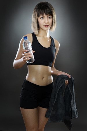 low key lighting: fitness woman shot in the studio low key lighting on a gray background holding water and a towel
