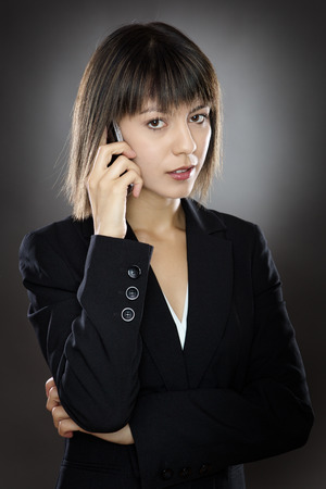 low key lighting: business woman chatting on a mobile phone low key lighting shot in the studio on a gray background Stock Photo
