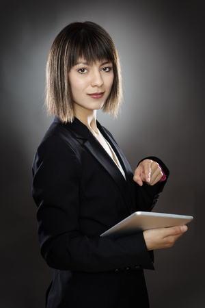 low key lighting: sharp looking business woman using a tablet computer shot in the studio low key lighting on a gray background