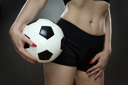 midriff: low key lighting of a woman holding a football against her midriff Stock Photo