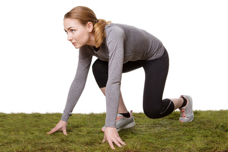 fitness woman in the get set ready go positions to run on grass Stock Photo