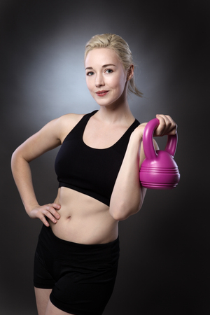 low key lighting: fitness woman holding a kettlebell shot in the studio low key lighting on gray background Stock Photo