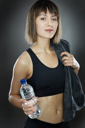 low key lighting: fitness woman shot in the studio low key lighting on a gray background holding water and a towel over her shoulder